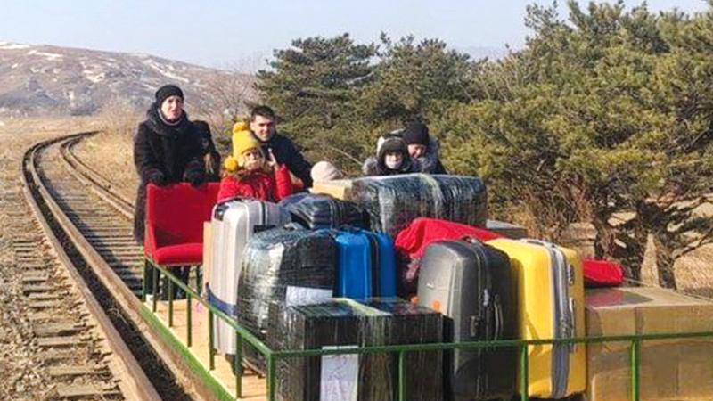 The group of Russian diplomats, which included children, pushed themselves for more than 1km over train tracks