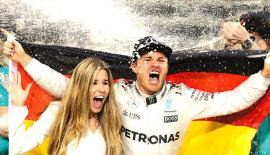Mercedes driver Nico Rosberg of Germany celebrates with his wife Vivian Sibold holding a German flag in the team garage after winning the F1 2016 Championship.