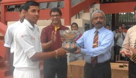 Ananda College principal S.M. Keerthiratne returns the L.D.H. Peiris memorial trophy to Royal captain Helitha Vithanage.