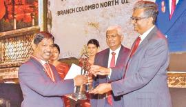 Ceylinco Life's Best Branch Head (Veteran category) S. Dharshan (left) receives his award from Vice Chancellor of the University of Sri Jayewardenepura Prof. Sampath Amaratunge.