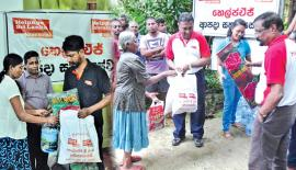 HelpAge Executive Director Samantha Liyanawaduge distributing food items to flood victims . Finance Manager Sumedha  Hastanayaka is also in the picture