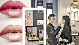A sales assistant helps a customer try out cosmetic products at a department store in Shanghai