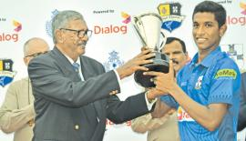 S. Thomas' College captain Dellon Peiris accepts the Mustungs Trophy from former Thomian skipper Umesh Idippily after his team crushed Royal College in their annual limited overs cricket match at the SSC ground in Colombo yesterday. Also in the picture are Royal College principal BA Abeyratne and S. Thomas' College warden Rev Marc Billimoria (Picture by Herbert Perera)