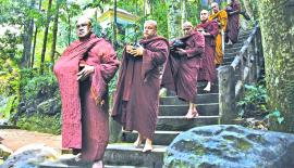 AGE-OLD RITUALS: Bhikkus walk on pindapatha under the forest canopy for the mid-day meal to the alms hall in Madakada Aranya