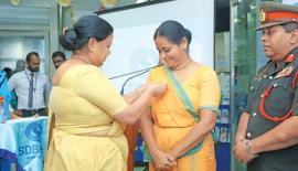 Mrs. Anoma Fonseka pins the flag on Mrs. Samadanie Kiriwandeniya