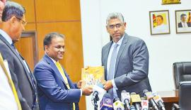 Sri Lanka Cricket president Thilanga Sumathipala (left) presents his annual accounts statement to Sports Minister Faizer Mushtapha at his ministry