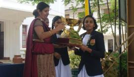 Maheshika Hewege the captain of the Mahamaya College swimming team receives the trophy from acting principal of the school Himali Senadheera