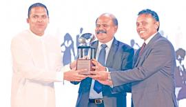 Chairman, Sri Lanka Telecom Group, P.G. Kumarasinghe Sirisena and  Chief Executive Officer, HCS, Roshan Kaluarachchi present a token of appreciation to Minister Harin Fernando.