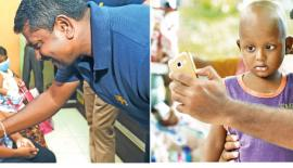 Rangana Herath talks to a child -Aggressive fast bowler Lahiru Kumara shows his gentle side as he takes a selfie with a young boy