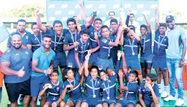The triumphant St. Joseph's College Under-14 rugby team comprising Anjika Athukorale, Rishon Mendis, Mark Lakidu, Santhush Matheesha, Ryan Fernando, Yevin Perera, Ivano White, Tharusha Jayasuriya, Vishika Fernando, Richy Dilusha, Randil Weeragoda, Nikhel Fernando, Senidu Eran, Aaran Bandara, Beeshma Jayasekara, Janith Marasinghe and Rehan Dewaka celebrate with their trophy. They were coached by  Ransilu Jayatilleke (at left)