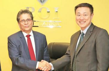 After the signing of the agreement. BOI Chairman Mangala Yapa with Sugih Energy Director Danny Lee.