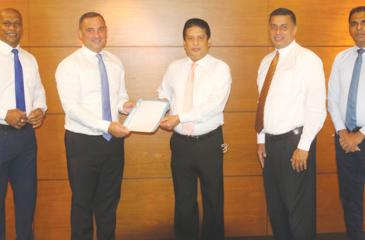 Exchanging the agreement: Country Manager Sri Lanka and the Maldives, Visa, Anthony Watson (second from left) presents the agreement to CEO DFCC Bank, Lakshman Silva. Director, MS & A Sri Lanka and the Maldives at Visa Worldwide Pte Ltd (first from left) Nalin Dissanayake, Vice President and Head of Cards, DFCC Bank (second from right) Denver Lewis and Manager, Merchant Acquiring, DFCC Bank (first from right) Chrishan Jayamanne look on.
