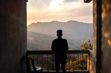 A police officer who fled from Myanmar following a military coup looks out to the mountains from an undisclosed location bordering Myanmar