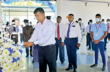 Rohana Dissanayake, Chairman, David Peiris Group  lights the  oil lamp while DPMC, Director (Vehicle Sales) Nalaka Madugalla (centre) and DPMC Director (Parts and  Accesories) Jayantha Ratnayake (right) looks on.