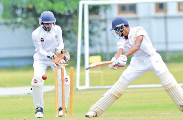 Ahan Wickremasinghe of Royal College looks behind to see his stumps shattered in their match against Wesley College at Reid Avenue yesterday (Pic. by Chinthaka Kumarasinghe)