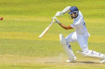 Dimuth Karunaratne raises his bat after reaching a double century