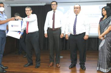 Flight Sergeant R. Devapriya receives a medical insurance cover from Director, People's Insurance and CEO and GM, People's Leasing, Shamindra Marcellin.