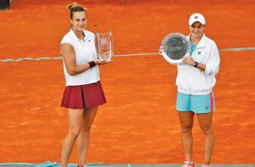 Aryna Sabalenka (left) with her prize after beating Ash Barty