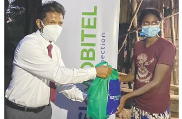 An SLT-Mobitel official presents a gift pack to a member of the indegenous community.