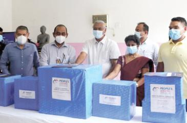 Minister Chamal Rajapaksa symbolically presents an essential equipment pack to the Medical Superintendent of Tangalle Hospital, Dr. Mrs. D.R.N. Saranasinghe. Minister Namal Rajapaksa, Chairman of People's Bank and People's Leasing, Sujeewa Rajapaksa (third from left) and the CEO of People's Leasing Shamindra Marcelline (second from left) look on.