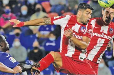 Luis Suarez heads the ball