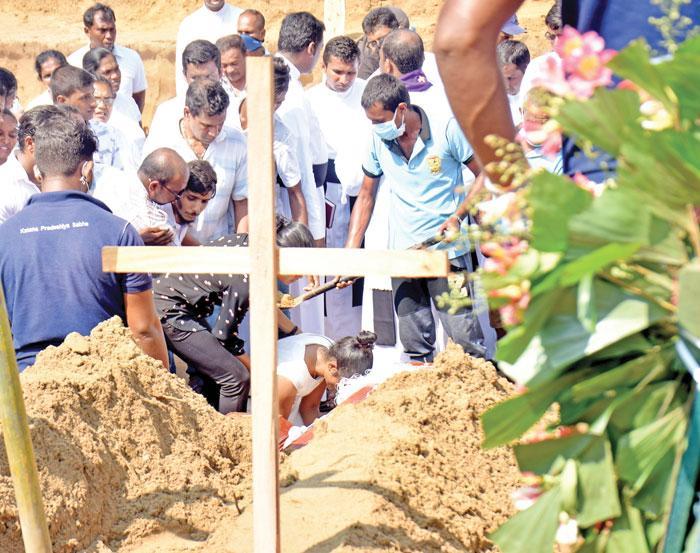 A girl weeping at a grave site    Pic: Gayan Pushpika