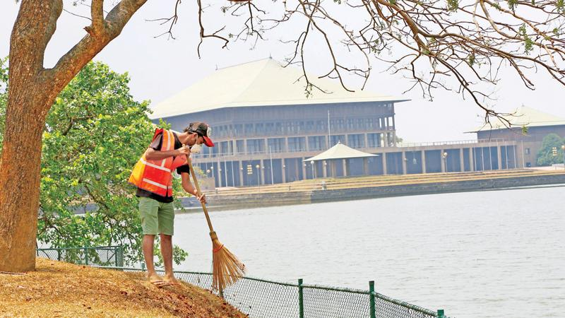 Amid the wide speculation about the dissolution of Sri Lanka's eighth Parliament this week, a worker of the Municipal Council, Sri Jayewardenepura, Kotte engaged in his daily routine of sprucing up the area yesterday. Unlike the previous elections, there is a growing demand to get rid of misfits and elect a people-friendly, educated 225 upright MPs to the new Legislature in order that the problems of the masses could be resolved.  Pic: Rukmal Gamage.