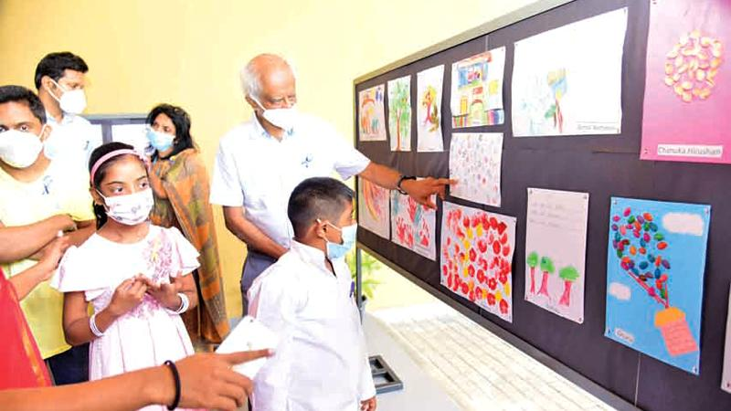 Emeritus Professor of Paediatrics Harendra de Silva points to a drawing by children with special needs