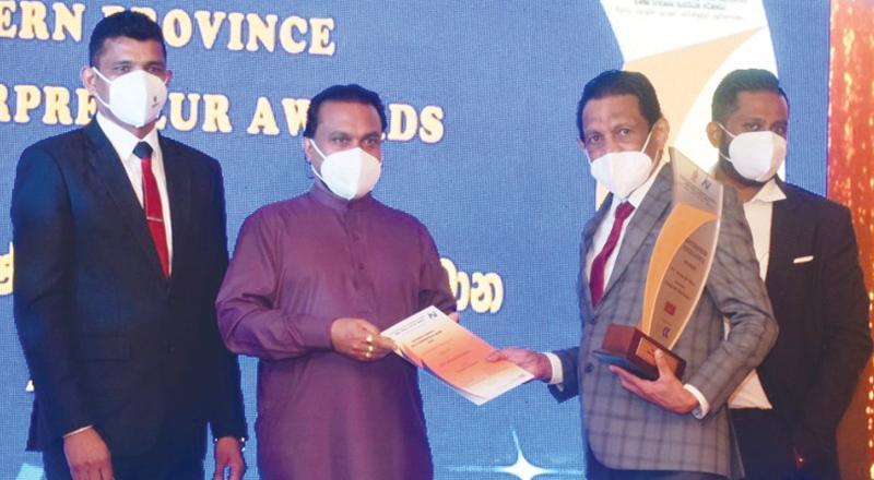 Chairman, Evergreen Group, Aruna de Silva receives the award from Minister Wimal Weerawansa.