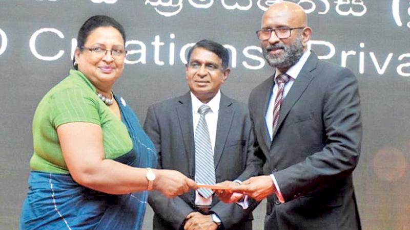 Naleen Edirisinghe, Senior Deputy General Manager of Pan Asia Bank presents the Merit award to officials of D & D Creations (Pvt) Limited