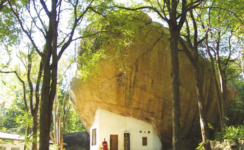 A bhikkhu's kuti built under a drip-ledge cave
