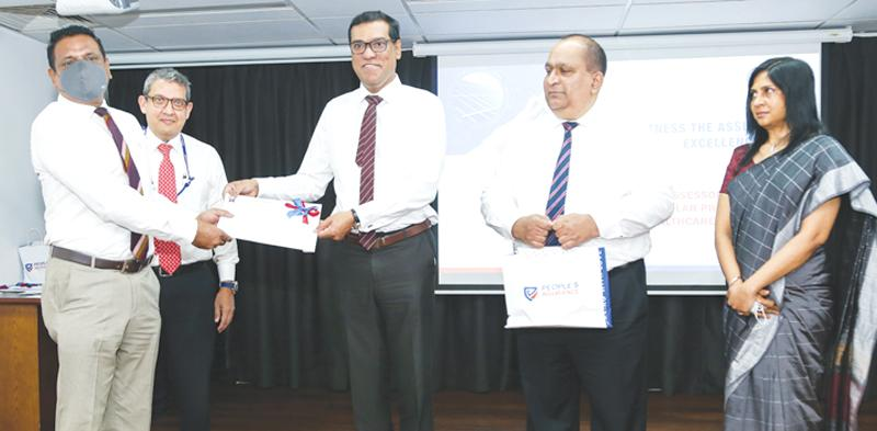 Royce Delpechitra receives solar panel policy from Director, People's Insurance and CEO and GM People's Bank, Ranjith Kodithuwakku. From left: Royce Delpechithra,  Director People's Insurance and CEO and GM People's Leasing, Shamindra Marcellin, Director, People's Insurance and CEO and GM People's Bank, Ranjith Kodithuwakku, CEO, People's Insurance, Deepal Abeysekera and Head of Operations, Mrs. Jeewani Kariyawasam.