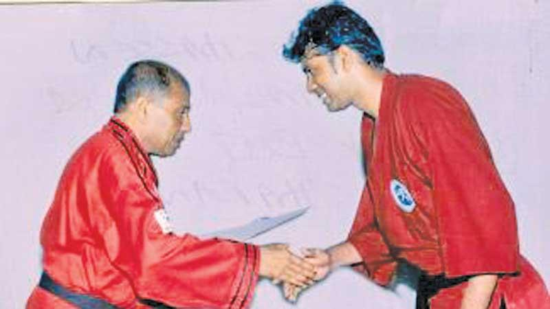 File photo of Hassen Khalid (left) presenting the black belt to T. Rangatharan