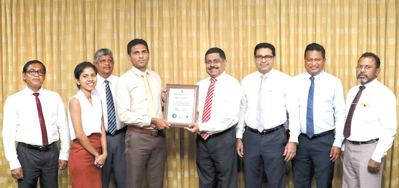 Commercial Bank›s Managing Director S. Renganathan, COO Sanath Manatunge and AGM Services, Chinthaka Dharmasena (fourth, third and second from right) and senior bank officers receiving the certificate from officials of the Sri Lanka Climate Fund.