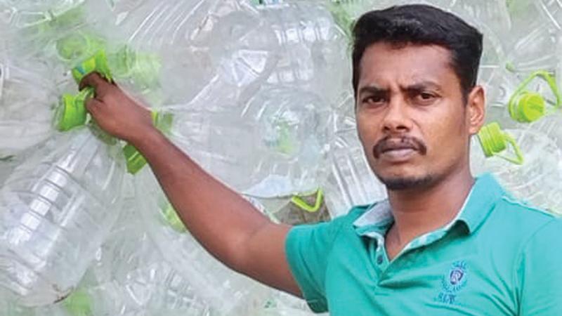 Mahesh standing beside the collectedPET plastic waste.