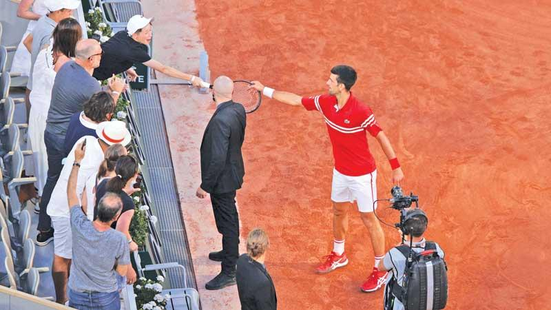 Novak Djokovic gives his Grand Slam winning racquet to a young boy in the crowd