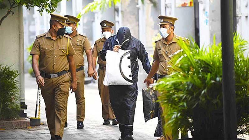 A suspect in the alleged rape of a 15-year-old girl at Mount Lavinia covers his face from the media prior to a court appearance