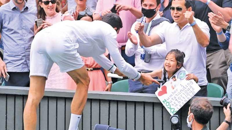 Novak Djokovic presents his racket to a young fan in the front row after his win at Wimbledon 2021