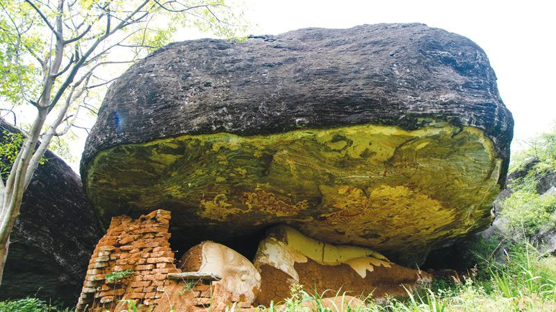 The Mailla rock cave with the reclining Buddha statue damaged by treasure hunters later retouched by someone or group