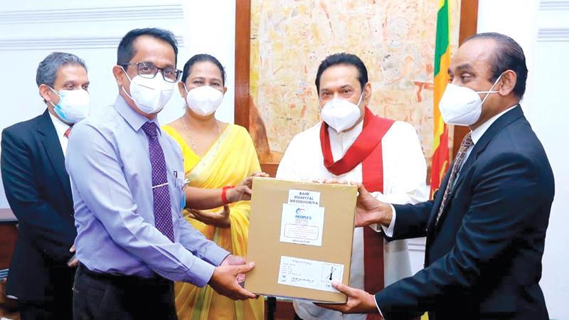 People's Leasing Chairman Sujeewa Rajapaksa and CEO Shamindra Marcelline make a token presentation to Prime Minister Mahinda Rajapaksa.