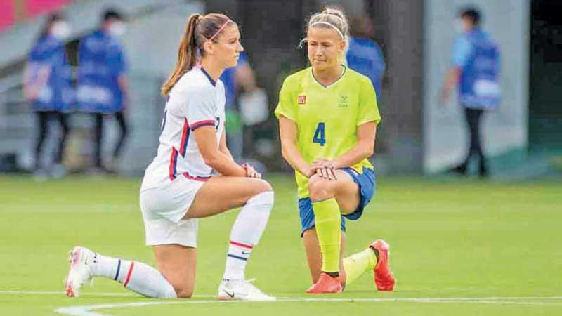 Women's football players from Sweden and the US take a knee bow before the start of their match at the Tokyo Olympics