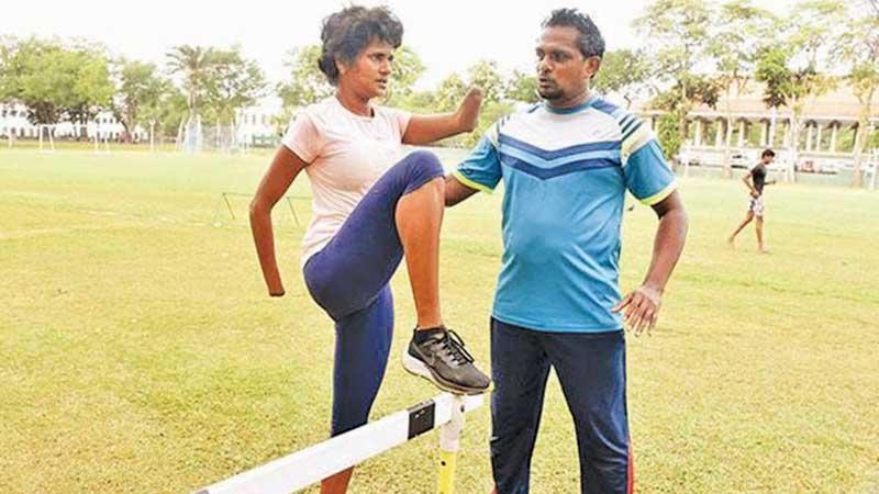 Harijan Ratnayake giving instructions to Para Olympic athlete  Kumudu Priyanka during a training session