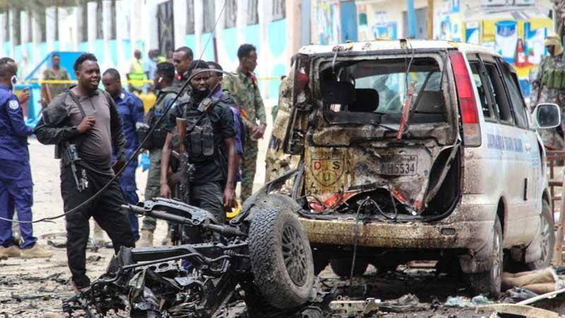 Security officers patrol on the site of a car-bomb attack in Mogadishu.